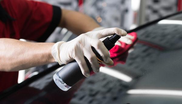 Closeup of hand spraying windshield